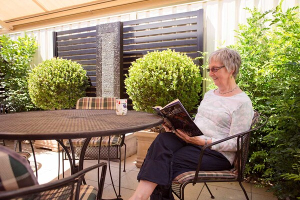Resident reading and enjoying the serenity in her private courtyard