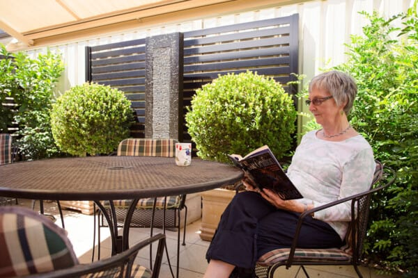 Resident reading in her low-maintenance backyard at Acacia on Marshall